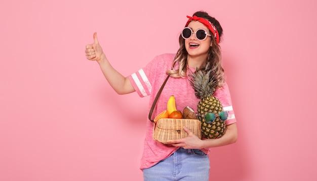 Портрет девушки со здоровой пищей, фруктами, на розовой стене