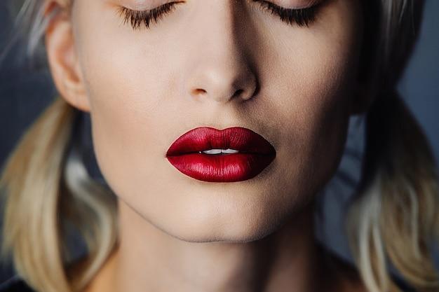 つや消しの赤い口紅と目を閉じた少女の肖像画。鎮静のクローズアップ。