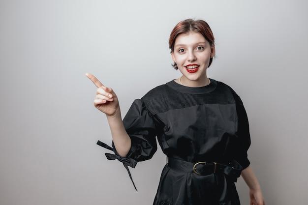 Портрет девушки с красными губами в модном черном платье на светлом фоне