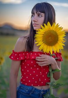 自然の中でひまわりを持つ少女の肖像画。スペインで撮影した写真。