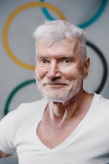 オリンピックの旗の前に白いtシャツを着た格好良い白髪の年配の男性の肖像画。スポーツとオリンピックのコンセプト