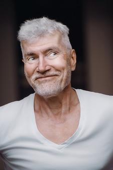 白いtシャツを着た格好良い白髪の年配の男性の肖像画。スポーツとヘルスケアの概念