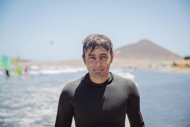 잘 생긴 인도 남자의 초상화, 해변에서 카메라를 바라보는 서퍼, 익스트림 스포츠, 여가 활동 - 얼굴에 초점을 맞춥니다.