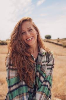 彼女の髪を横にしてカメラに微笑んでいるハンサムな女性の肖像画