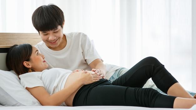 Портрет красивого молодого азиатского мужчины и женщины, лежа на кровати вместе. они счастливо улыбаются и касаются живота беременной матери.
