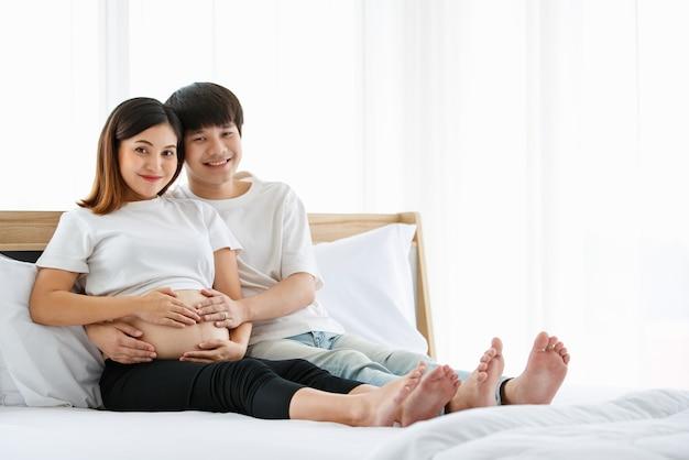 Портрет красивого молодого азиатского мужчины и женщины в белой ночной рубашке, сидящих на кровати вместе. они счастливо улыбаются и касаются живота беременной матери.