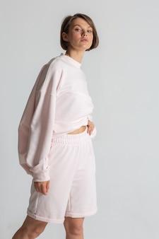 白い背景にカジュアルなスウェットシャツとショートパンツを着ているハンサムな若い女性の肖像画