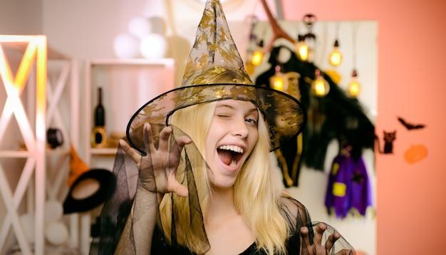 黒のドレスとオレンジ色の壁にカボチャの帽子のゴージャスな金髪の魔女の肖像画。ハロウィーンの壁にポーズをとる美女。