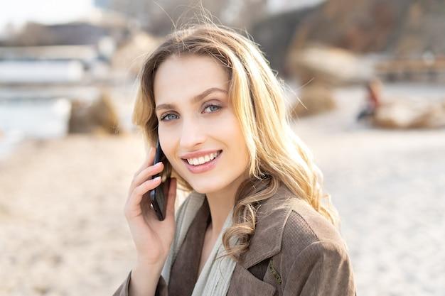 笑顔で携帯電話で話し、カメラを見ているゴージャスな金髪の若い女性の肖像画