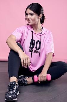 ピンクのダンベル運動ピンクスポーツパーカーでゴージャスなボディ肯定的なラテン女性の肖像画
