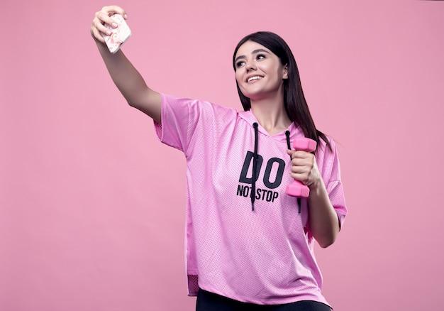Портрет шикарной фигуры позитивной латинской женщины в спортивной толстовке с розовыми гантелями, делающей селфи на телефон на розовом