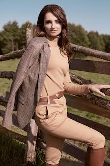 Портрет великолепной брюнетки в элегантной клетчатой коричневой куртке позирует на деревенском пейзаже