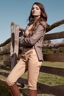 田舎の風景にポーズをとってエレガントな市松模様の茶色のジャケットでゴージャスなブルネットの女性の肖像画