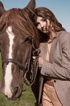 Портрет великолепной брюнетки в элегантной клетчатой коричневой куртке, позирующей с лошадью на деревенском пейзаже