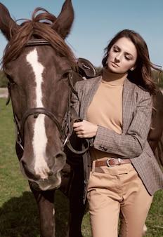 田舎の風景に馬とポーズをとってエレガントな市松模様の茶色のジャケットでゴージャスなブルネットの女性の肖像画