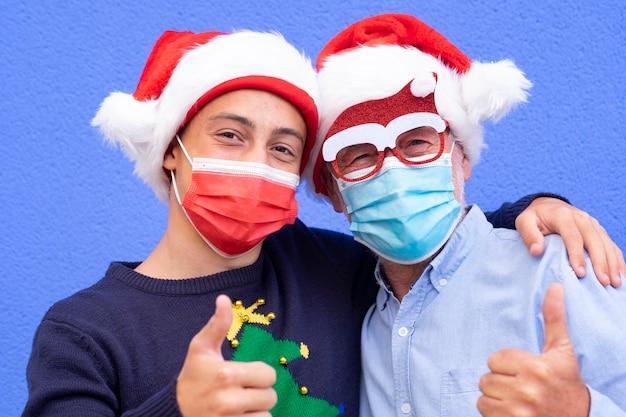 코로나바이러스와 산타 모자로 인해 마스크를 쓰고 손으로 미소를 짓고 있는 10대 손자와 할아버지의 초상화. 가족의 개념과 미래에 대한 긍정적인 희망