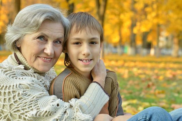 秋の公園で孫と祖母の肖像画