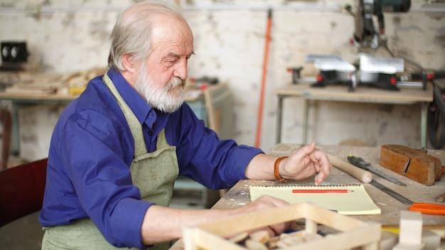 Портрет седого плотника за столом в мастерской с различными инструментами для ручной работы