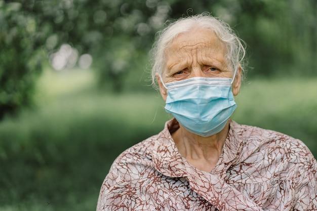Портрет седой грустной старухи в защитной маске в одиночестве во время карантина по covid-19.