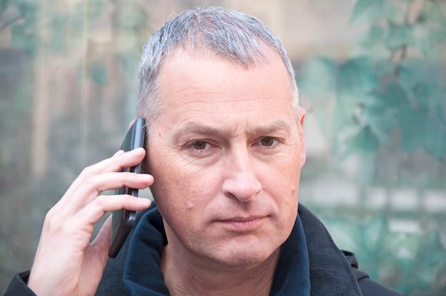 Портрет серый волосатый человек в разговоре через мобильный телефон. Premium Фотографии