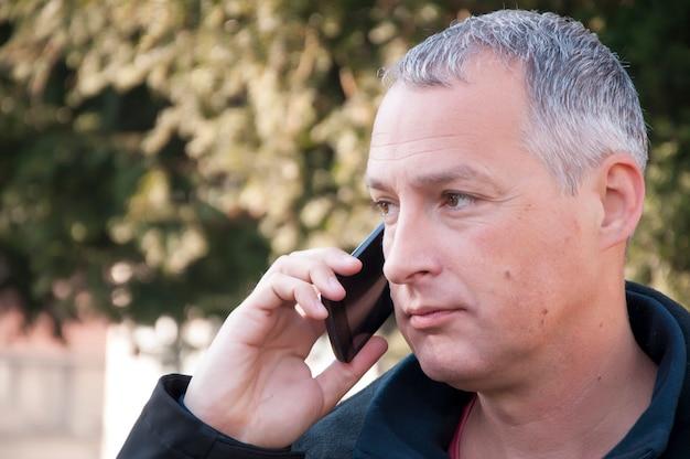Портрет серый волосатый человек в разговоре через мобильный телефон.