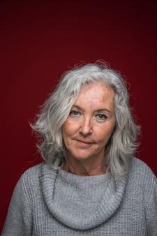 Портрет серой старшей женщины, стоя на красном фоне
