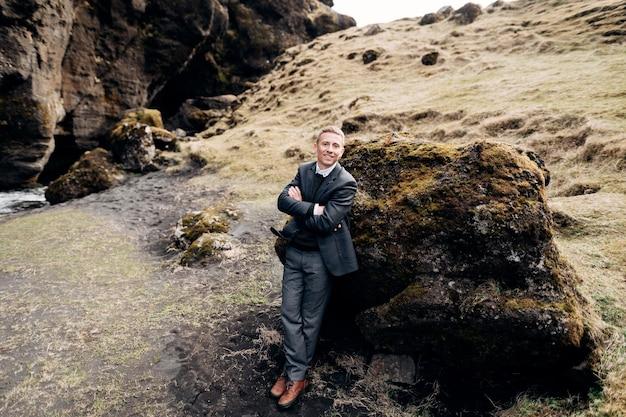 Портрет жениха, опирающегося на камень во мхе у скалистой расселины с горной рекой