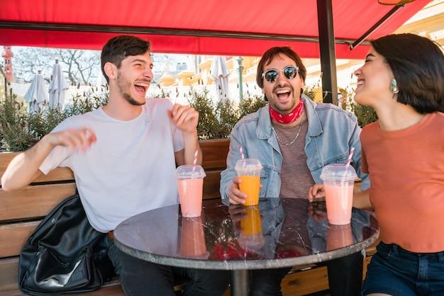 Портрет группы друзей, весело проводящих время вместе и хорошо проводящих время, попивая свежий фруктовый сок в кафе. концепция образа жизни и дружбы.