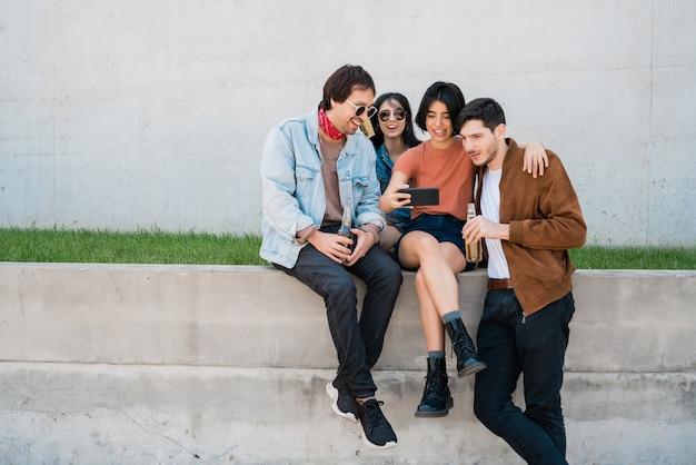 Портрет группы друзей, весело проводящих время вместе и весело проводящих время, делая селфи с помощью мобильного телефона. концепция образа жизни и дружбы.