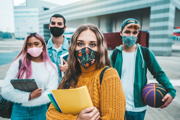 フェイスマスクで覆われた学生のグループの肖像画。コロナウイルスのパンデミックで若者が学校に通う新しい通常のライフスタイルの概念。
