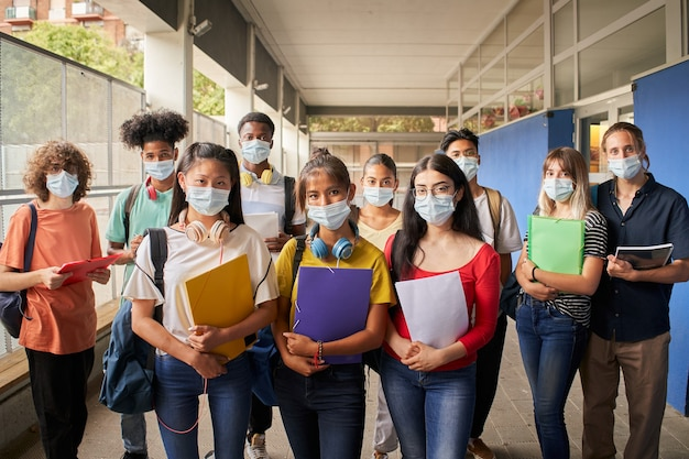 학교에 다시 카메라를 보고 얼굴 마스크에 학생 그룹의 초상화