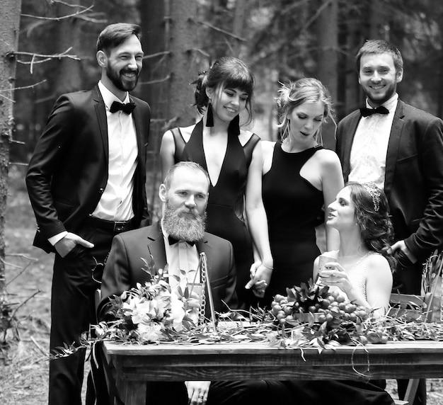 森の中のピクニックテーブルの近くのゲストと新婚夫婦の肖像画
