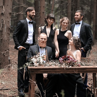 Портрет гостя и пары молодоженов у столика для пикника в лесу