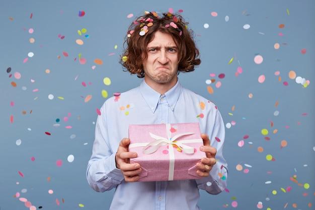 좌절 된 표정으로 선물 상자를 들고 남자의 초상화