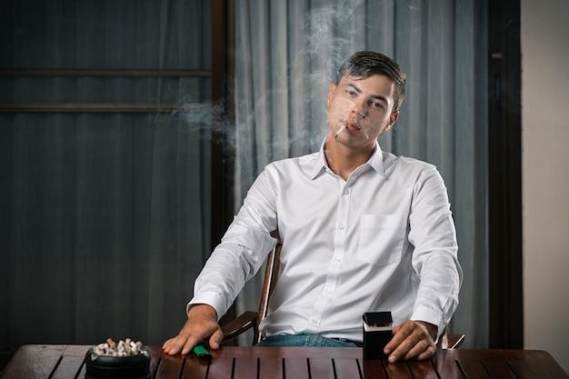 Портрет парня, позирующего сидя за столом, на котором стоит пепельница, полная сигарет