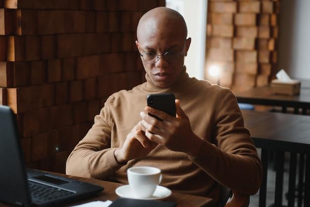 Портрет парня, использующего мобильный телефон и ноутбук
