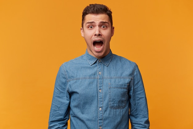 Портрет парня, который кричит в панике, кричит от страха, громко кричит, когда он поражен и очень напуган