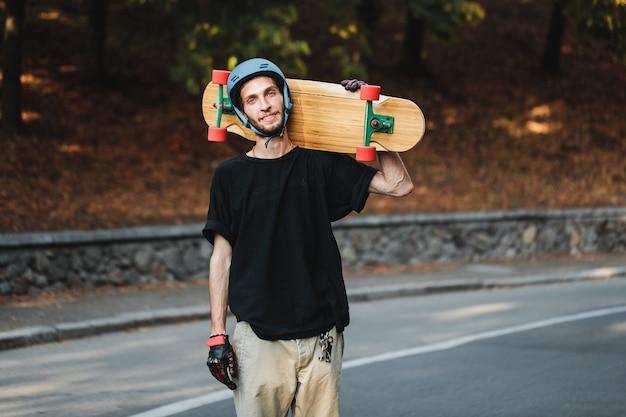 彼の肩にロングボードを持っている男の肖像画。夏のスケートボード。高品質の写真
