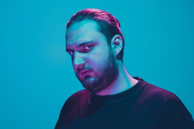 青いスタジオの背景にカラフルなネオンの光を持つ男のポートレート。落ち着いた真面目なムードの男性モデル。