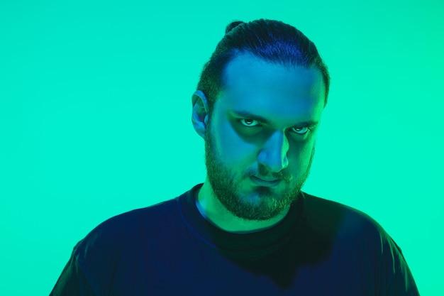 緑のスタジオの背景にカラフルなネオンの光を持つ男のポートレート。落ち着いた真面目なムードの男性モデル。
