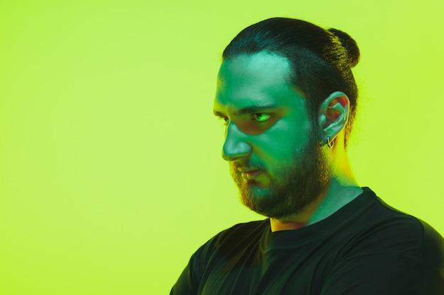 Портрет парня с красочным неоновым светом на зеленом фоне студии. модель-мужчина со спокойным и серьезным настроением.