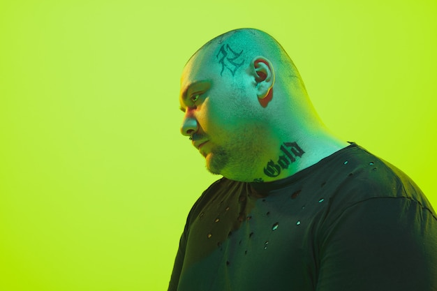Портрет парня с красочным неоновым светом на зеленой стене. модель-мужчина со спокойным и серьезным настроением. выражение лица, образ жизни миллениалов и внешний вид. будущее, технологии.