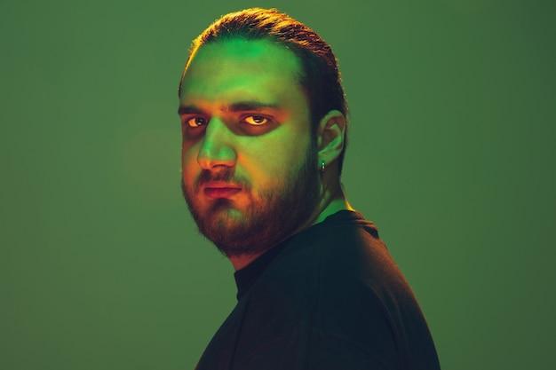 緑の壁にカラフルなネオンの光を持つ男の肖像画。落ち着きと真面目なムードの男性モデル。表情、ミレニアル世代のライフスタイルとのように見えます。未来、テクノロジー。