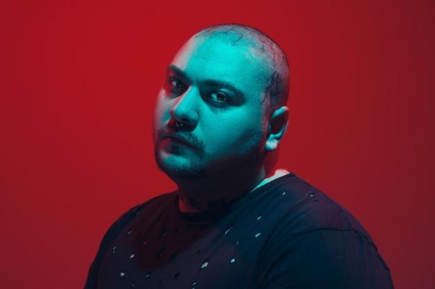 赤い背景のサイバー パンク コンセプトにカラフルなネオンの光を持つ男の肖像 Premium写真