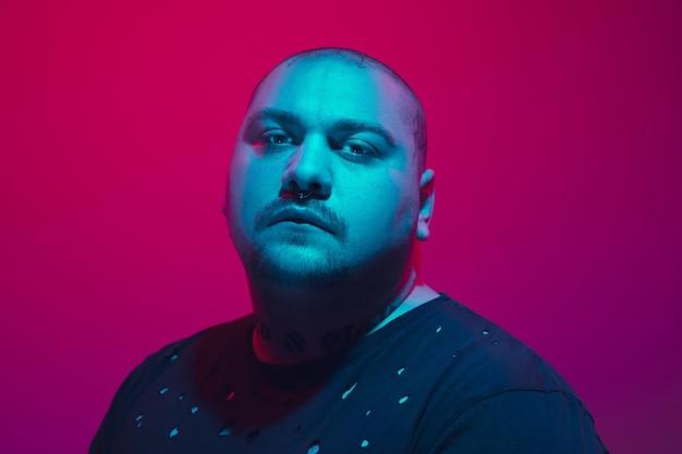 赤い背景のサイバー パンク コンセプトにカラフルなネオンの光を持つ男の肖像
