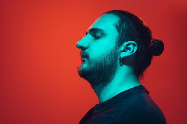 赤いスタジオの背景にカラフルなネオンの光を持つ男のポートレート。落ち着いた真面目なムードの男性モデル。