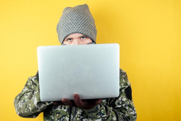 Портрет хакера-террориста в камуфляже и маске смотрит на ноутбук.