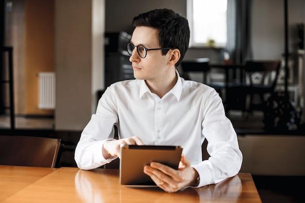 コーヒーショップの机に座っているタブレットを持って目をそらしている白いシャツと眼鏡を身に着けているハンサムな大人のマネージャーの肖像画。