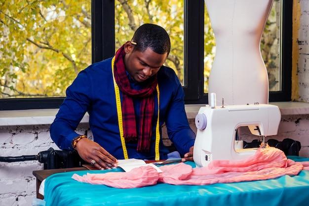 Портрет красивого африканского человека, улыбающегося швея со швейной машиной. стильный дизайнер африо-американца, работающий в манекене мастерской портного, измерительная лента таблицы в комнате против осеннего окна