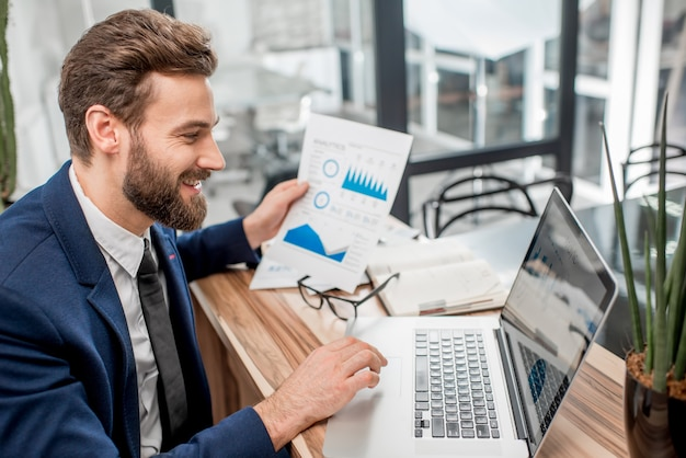 Портрет красивого аналитического менеджера, работающего с бумажными диаграммами и ноутбуком в офисе